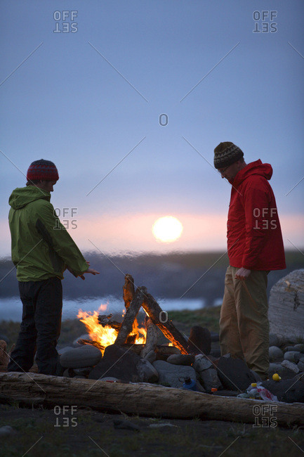 Two men stand around a camp fire on The Lost Coast, California.