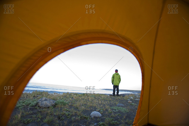 A man is seen through a tent door on The Lost Coast, California.