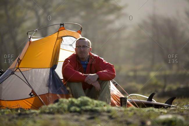 A man sits outside his tent on The Lost Coast, California.