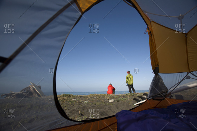 Two men sit on the beach outside their tent on The Lost Coast, California.