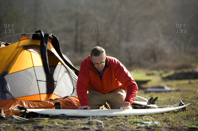 A man waxes his surfboard outside his tent on The Lost Coast, California.