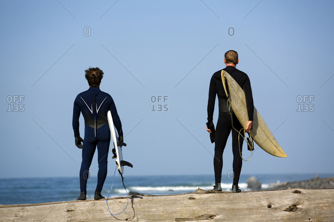 Two men stand with surfboards under their arms on The Lost Coast, California.