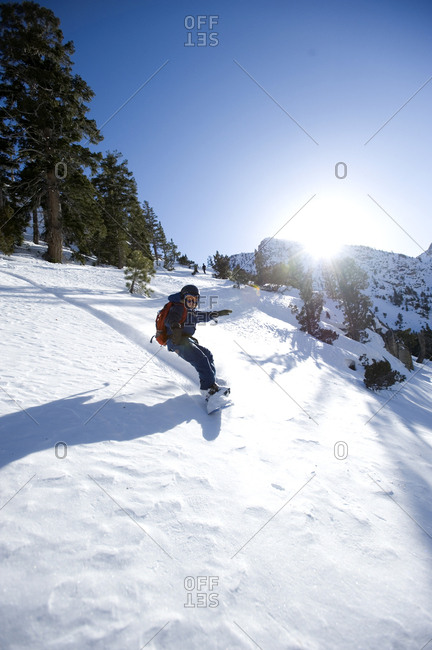 A boy snowboarding in the California backcountry.