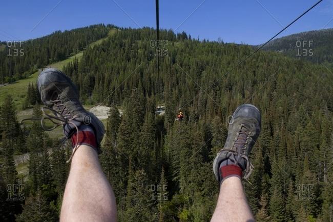 Two men ride a zip line at Whitefish Mountain Resort.