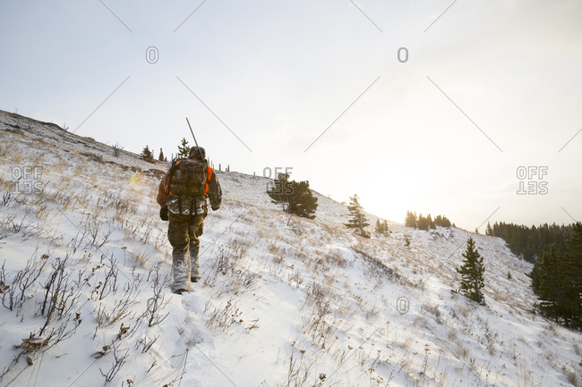 A male hunter at sunrise in the snow.