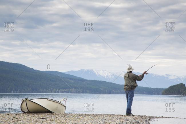 A man fishing on Whitefish Lake in Whitefish, Montana.