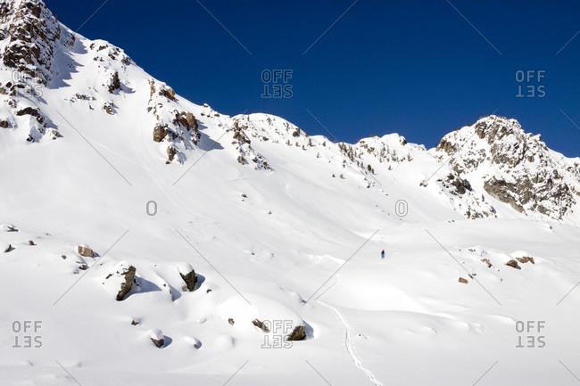 A male backcountry skier skins through fresh snow in the Beehive Basin near Big Sky, Montana.