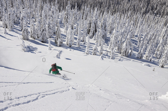 Male Skier Makes A Turn In Fresh Powder While Skiing In The Whitefish Range