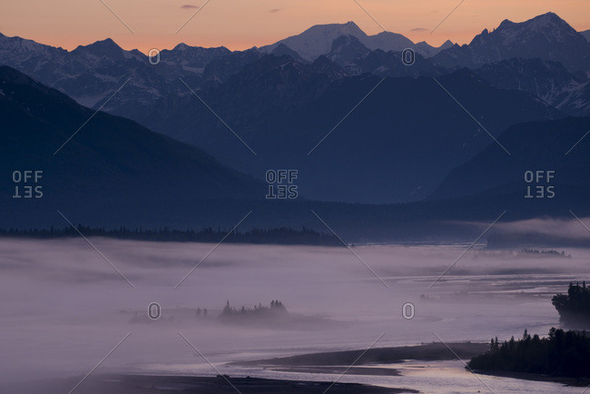 A thin layer of fog blanketed over a river and evergreens with mountains in the background at sunset.   Denali National Park, Alaska, USA.
