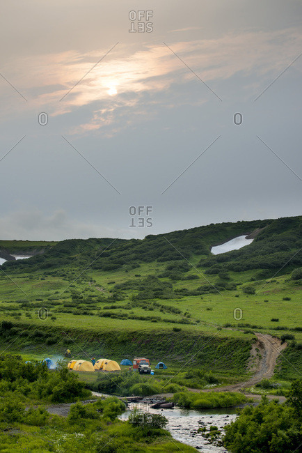 Tents and large trucks in wilderness by a river.  Kamchatka, Russia