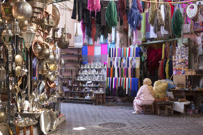 A moroccan woman dressed in typical dressing sitting outside a shop full of goods and souvenirs in the souk of Marrakesh, Morocco