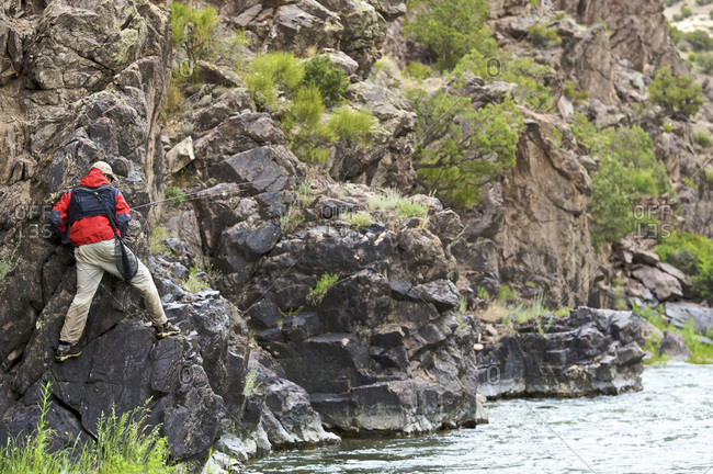 A fisherman climbs a rocky bank to avoid deep water on a river.