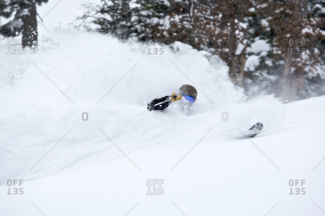 A man skiing through deep powder snow.