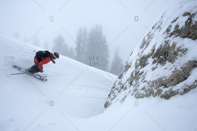 A man skiing next to a rock in Jackson Hole, Wyoming.