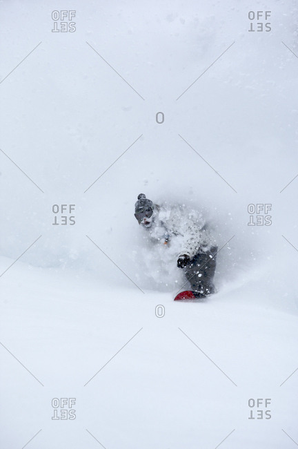 A man snowboards through deep snow.
