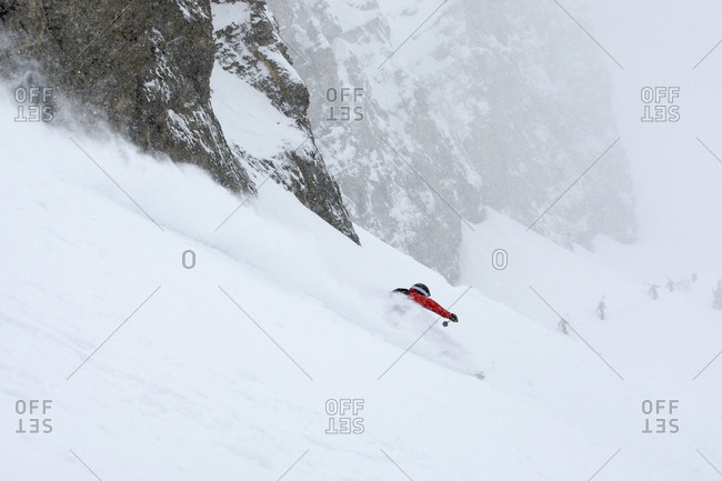 A man skiing beneath a cliff in Jackson Hole, Wyoming.