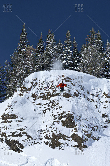 A man skiing off a cliff into a deep pillow of snow in Jackson Hole, Wyoming.