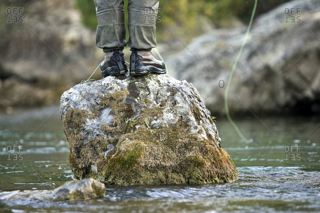 A man fishes from a rock on a river in Wyoming.