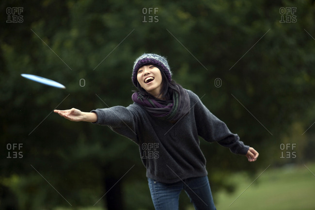A young Asian-American woman throws a flying disk while playing flying disk golf in Baltimore, Maryland.