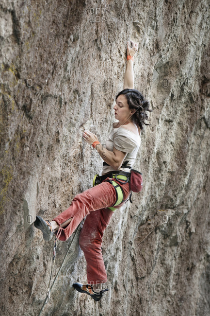 A middle aged woman wearing white t-shirt and red pants rock climbing in Jilotepec, Estado de Mexico, Mexico.