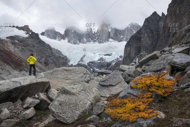 Female hiker standing in rocky scenery with glacier and mountains, Los Glaciares National Park, Patagonia, Argentina