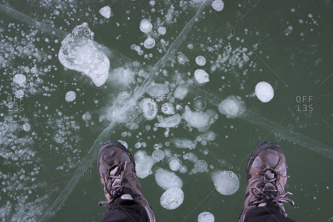 Man standing on translucent cracked ice wearing hiking shoes