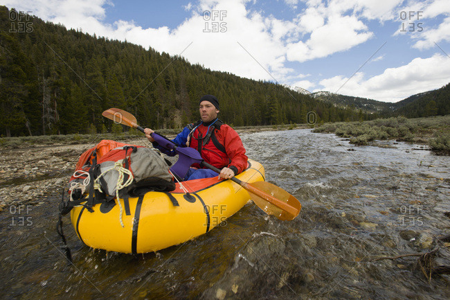 A young man paddles his small, inflatable raft at the source of the Salmon River in Idaho.