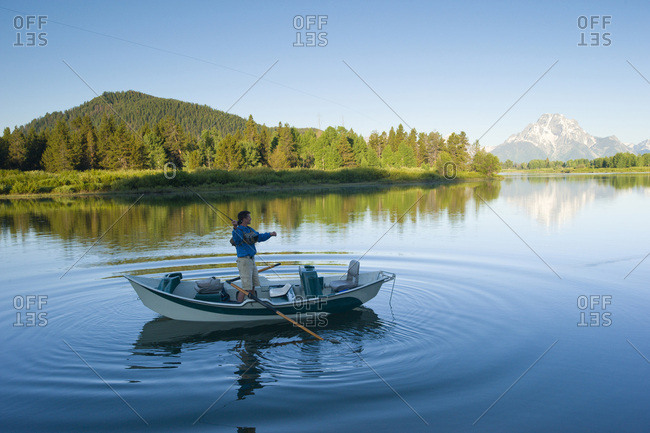 A man fly fishes in the early morning from his drift boat.