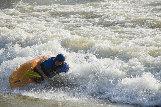 A male whitewater kayaker plays on the Missoula playwave.