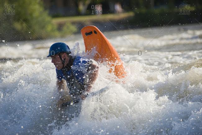 A male whitewater kayaker playboats on the Missoula playwave.