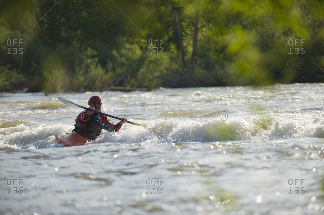 A male whitewater kayaker front surfs a wave.