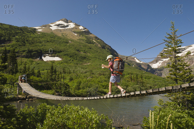 A young girl hikes over a suspension bridge in Glacier National Park, Montana.