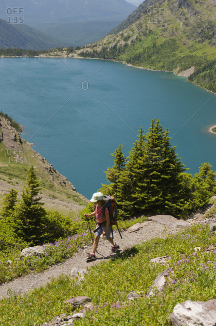 A young girl hikes a trail overlooking a alpine lake in Glacier National Park, Montana.