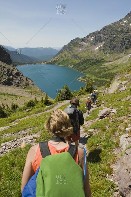 A group of backpackers hike down a trail towards an alpine lake, Glacier National Park, Montana.