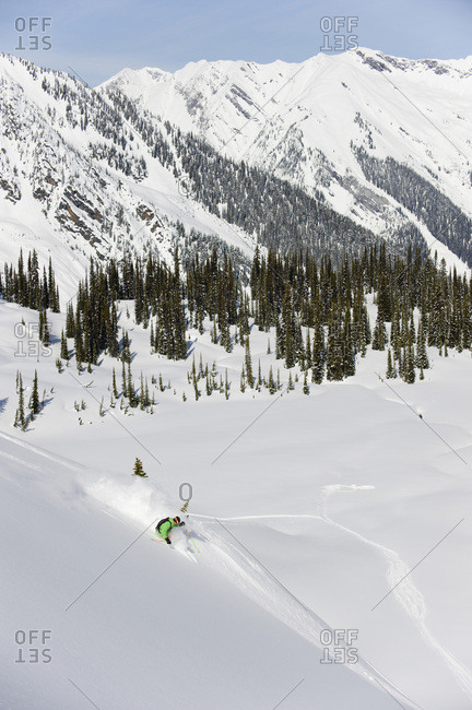 A backcountry skier enjoys the powder down to the valley floor of the Selkirk Mountains, British Columbia, Canada.