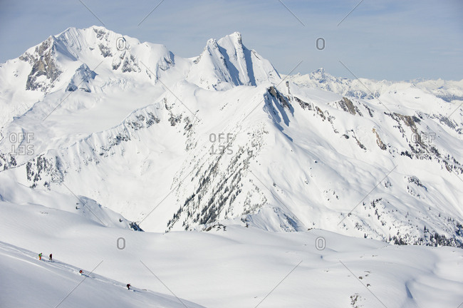 A group of backcountry skiers ski a wide open, alpine run in the Selkirk Mountains, Canada.