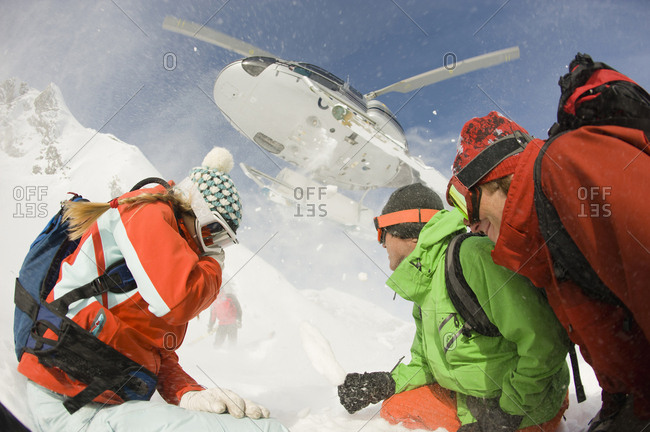 A group of skiers watch as their helicopter takes off from the drop zone in the Selkirk Mountains, Canada.