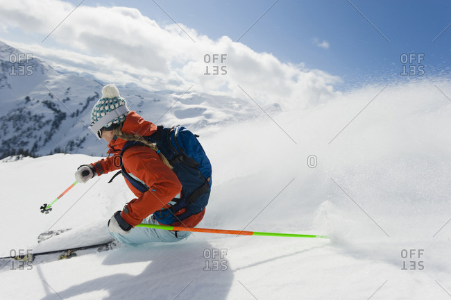 A woman skier speeds down an alpine bowl in the backcountry in the Selkirk Mountains, Canada.