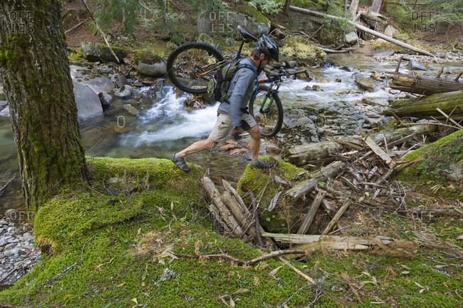A man carries his mountain bike over a washed out portion of a trail in northern Idaho.