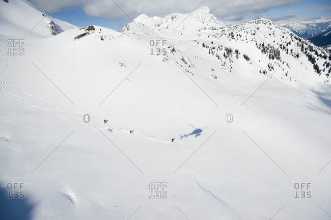 A group of skiers take a run down a large alpine bowl in the backcountry while the shadow of their helicopter is follows.