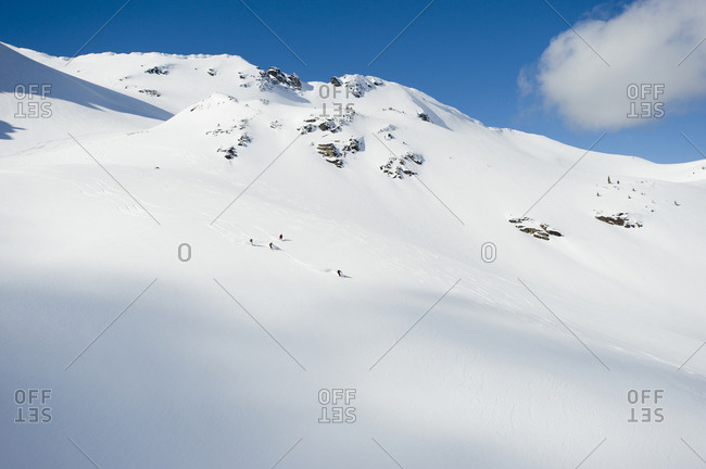 A group of skiers take a run down a large alpine bowl in the backcountry of the Selkirk Mountains, Canada.