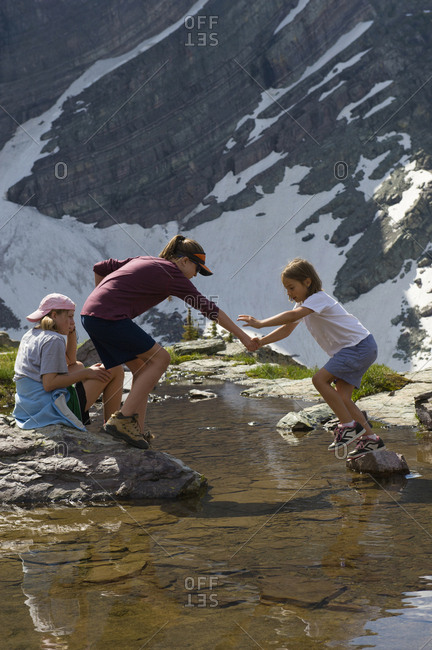 A young girl helps her sister cross a pool of water and onto a rock in Glacier National Park, Montana.