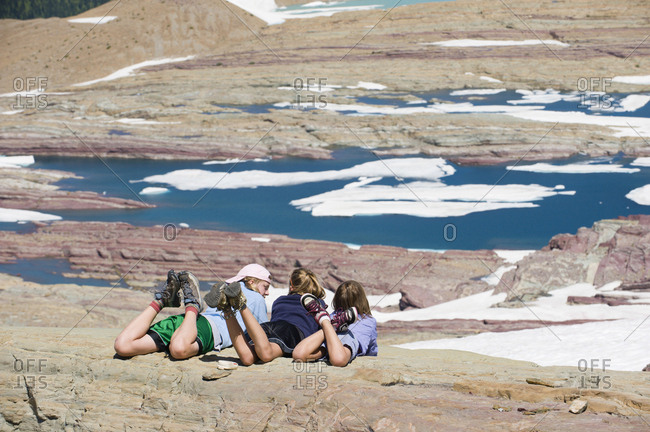 Three young girls relax and soak up the sunshine overlooking a glacier lake in Glacier National Park, Montana.