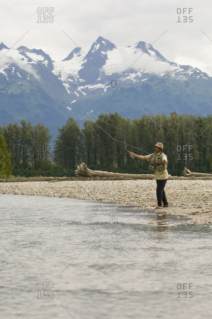A man fly fishes a stream in northwestern British Columbia along the coastal mountains of Canada.