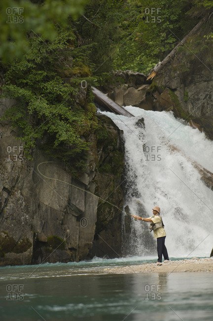 A man fly fishes a clear mountain stream in British Columbia, Canada.