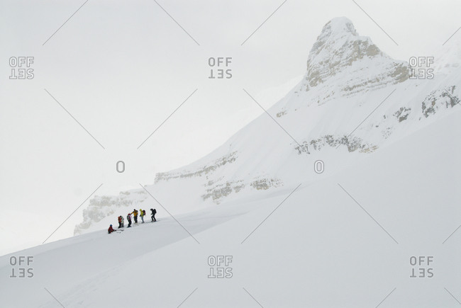 A group of backcountry skiers take a break on a ridge in the high alpine of the Canadian Rockies.