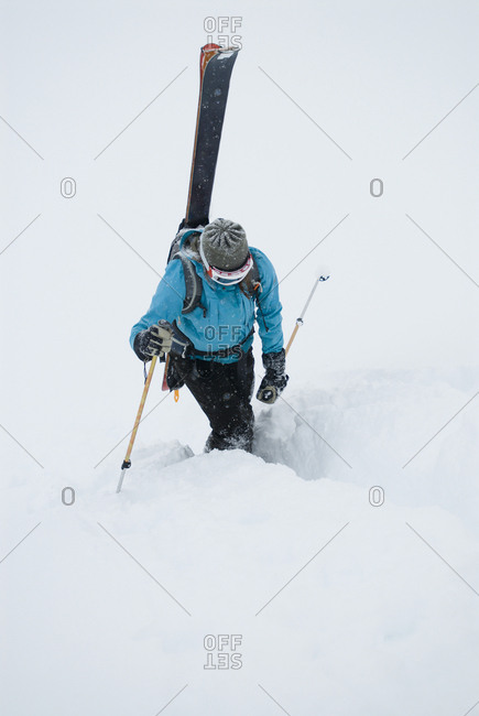A young woman packs her skis and kick steps up a section of trail in the backcountry of the Canadian Rockies.