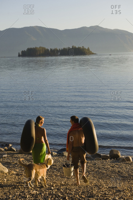 A young couple prepare to float on the lake in inner tubes during a hot summer day.