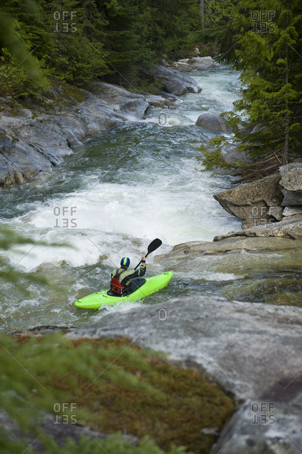 A whitewater kayaker sets up for a drop on a high mountain river.