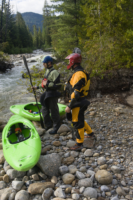 Two whitewater kayakers prepare to boat a high mountain stream.